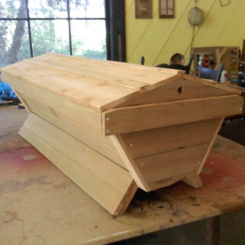 Unpainted top bar hive sitting on my studio table.