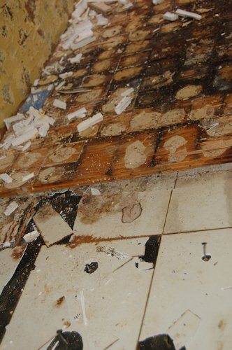 See the crumbled white Formica beneath the layer that once had blue tiles?